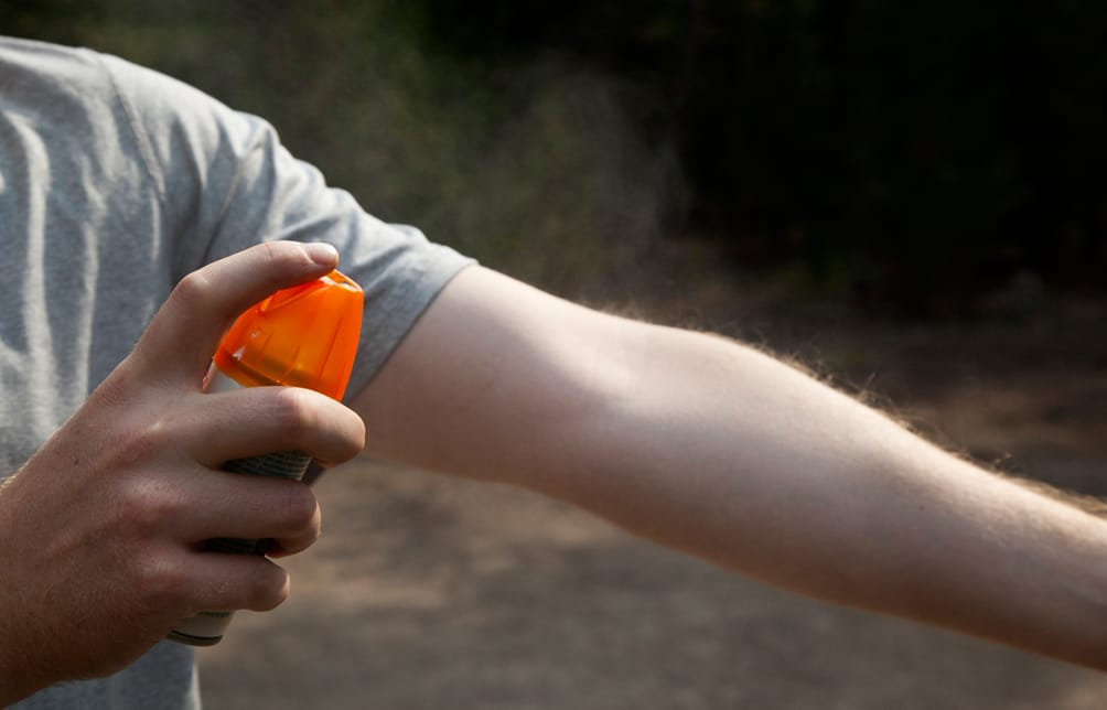 Person applying insect repellent spray