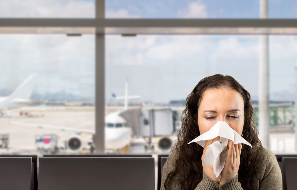 Woman sneezing in an airport